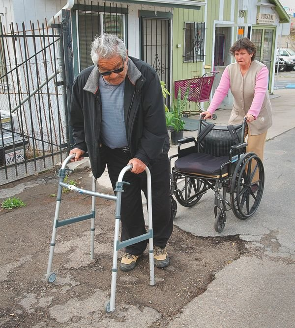 Juan Mariscal struggles to navigate San Ysidro's crumbling sidewalks using his walker or in his wheelchair (his wife Irma behind him).
