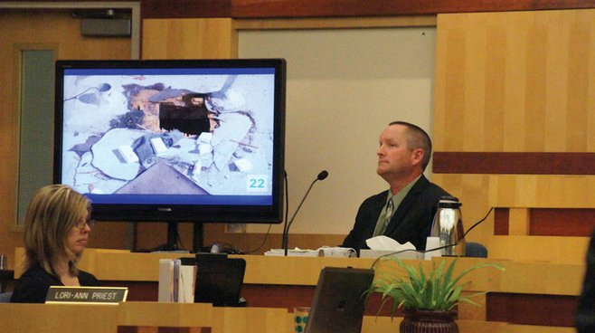 Officer Patrick Preston testifies next to a screen displaying a photo of the hole in the jewelry store's roof.