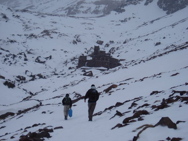 Hiking through the snow with Refuge du Toubkal up ahead