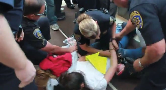 "Ashley Wardle being handcuffed: ""A cop grabbed me by my backpack and pulled me inside the building."""