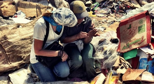 Volunteer comforting a child, one of Tijuana's destitute poor living at the Montana de Basura.