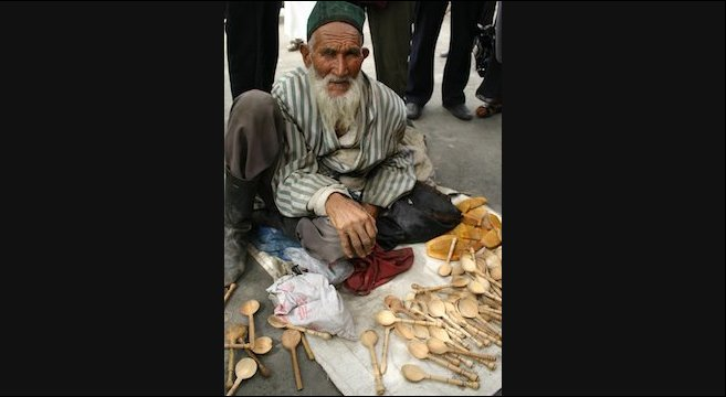 An old man selling spoons painstakingly carved with a pocketknife on the street in Kashgar.