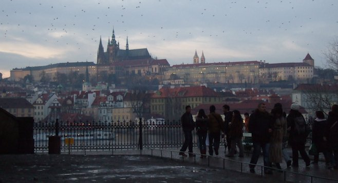 Approaching the Charles Bridge at dusk, the author's greeted by the 9th-century Prague Castle rising above the river.