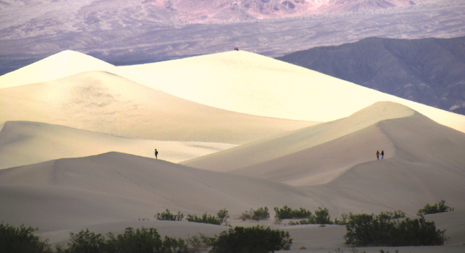Hikers ascending Death Valley's massive sand dunes take in the wonder.