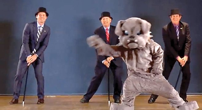 Missed his calling?  City attorney Jan Goldsmith (left) dances behind someone in a dog suit.
