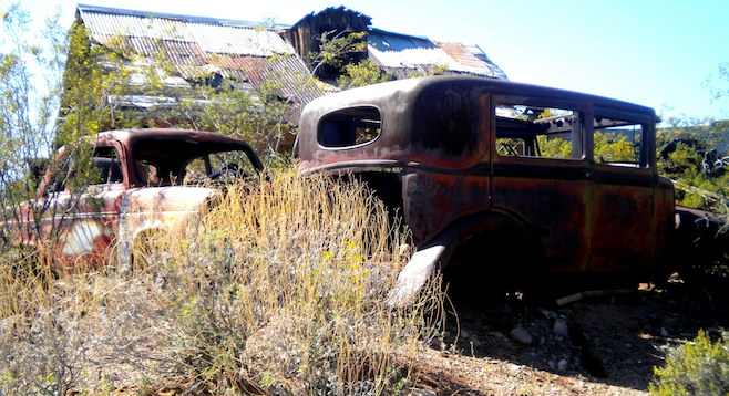 Rusted-out shells of old cars in Vulture City.