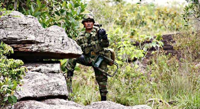 A sniper keeps watch for FARC guerrillas near Caño Cristales.