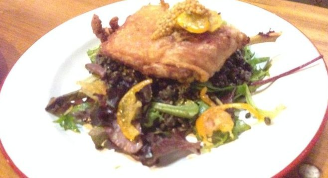 Crispy duck on a bed of lentils and greens, topped by pickled mustard seeds.
