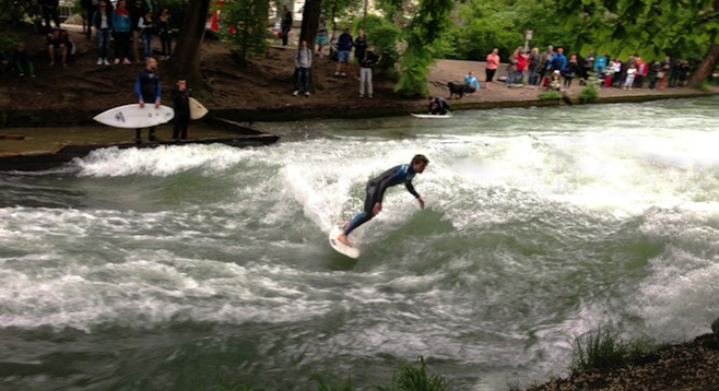 A crowd watches river surfers in Münich.