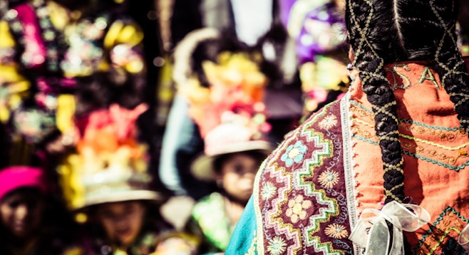 Peruvian woman in traditional dress at the market. (stock photo)