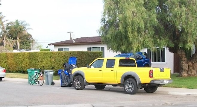 Person rummaging through recycling bin in Imperial Beach.