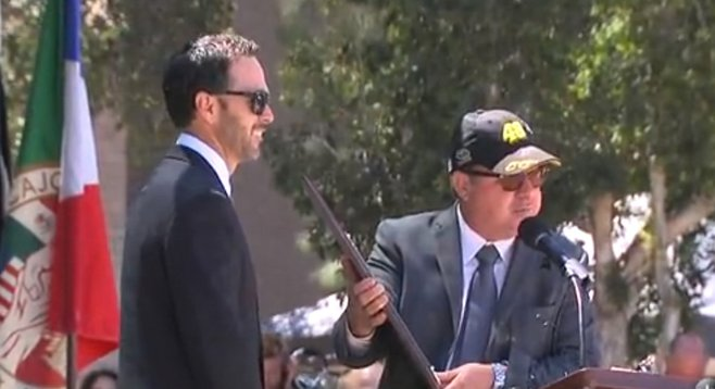 "El Cajon Mayor Bill Wells hands Johnson a personalized 12-gauge shotgun, ""The only key our city will ever need."""