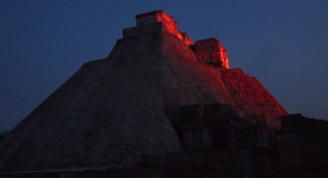 Uxmal's centerpiece, the Pyramid of the Magician, lit up at night.