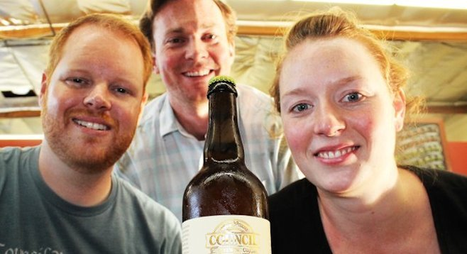 Council's Jeff Crane (background), Curtis and Liz Chism pose with a bottle of their first barrel-aged beer, Nicene