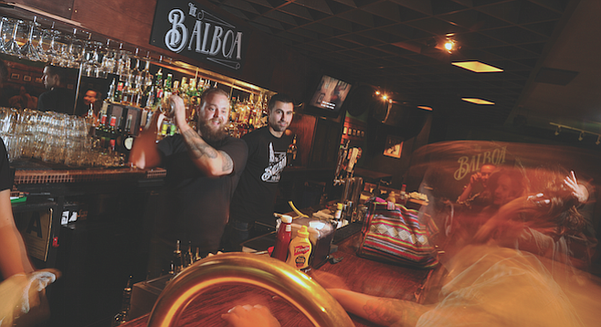 Tommy (left) mixes a drink at the refined Banker's Hill bar.
