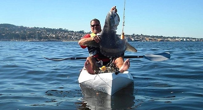 Avid kayak angler Craig MacDonald from Carmel holding a smallish mola with a big bite out of it. Craig said the