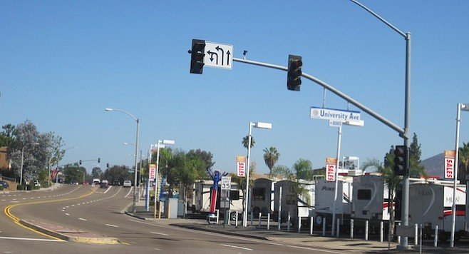 Baltimore Drive at the corner of University. In the distance (far right) is a signal light. The right turn leads to I-8 east; the left turn to El Cajon Blvd.