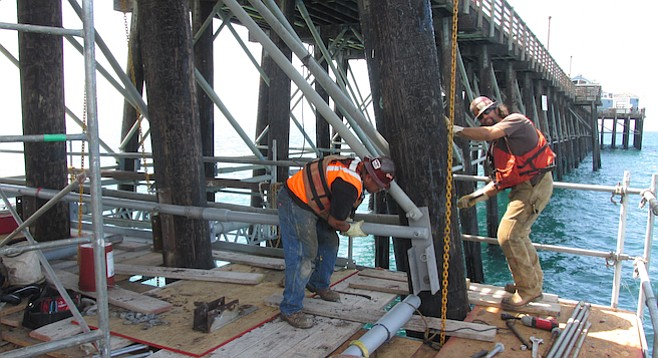 Work crew aligning and pounding in bolts to support crossbeams