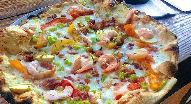 White-sauce pizza with shrimp, bacon, star zucchini, peppers, and nopales