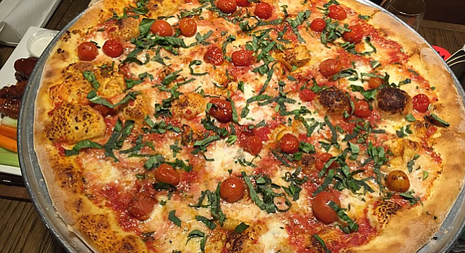 The New York–style Margherita pizza is topped with roasted cherry tomatoes.