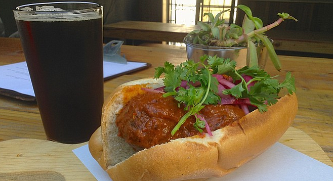 Beef-and-bacon meatball sandwich with chipotle sauce and a brown ale