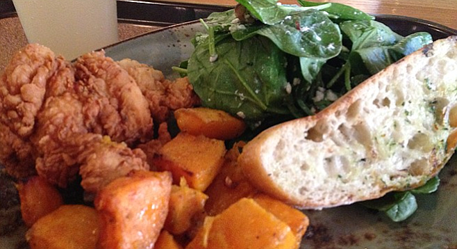Boneless fried chicken served with roasted butternut squash, spinach salad, and slice of toast