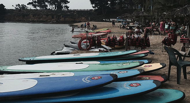 Paddleboards stacked on Carlsbad Lagoon's beach.
