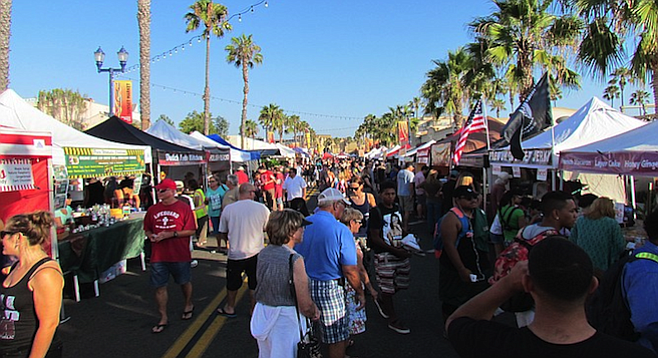 Crowds stroll Sunset Market along Pier View Way.
