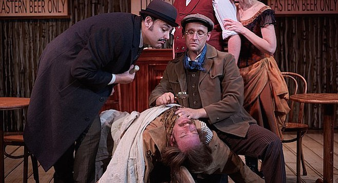 Sherlock Holmes (Jason Maddy) surrounded by suspects.