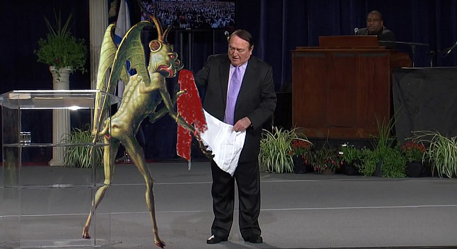 "Happier Times: Beelzebub presents Cerullo with a prayer shawl soaked in the Blood of the Worthless Poor at a 2014 Prosperity Gospel Conference. ""Back then, I thought we would go on and on,"" recalls the disappointed demon. ""You can't see it in the photo, but my butt-face is smiling from cheek to cheek!"""