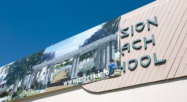 Developer's banner on the former school's façade advertises a video