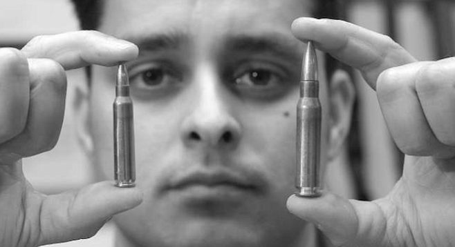 "James Montes, holding .223 and .308 caliber bullets. ""Gone is the day of trench warfare like in World War II and World War I. You are not having to pick guys off at 500 yards."""