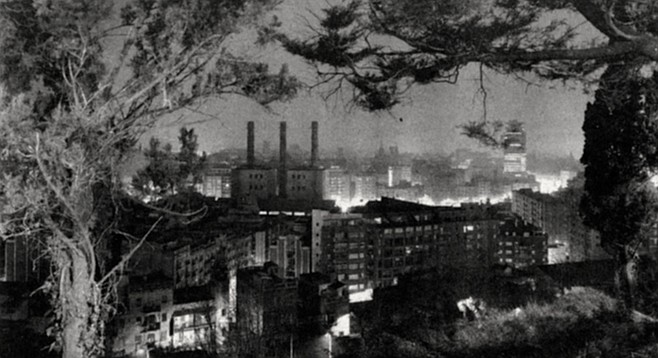 Barcelona Through the Trees, 1982. It's night. Seen from a high vantage point, through a framing wreath of trees, the city looks as if it's on fire.