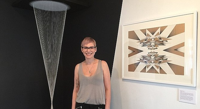 Artist Melissa Walter with two of her works, an installation piece and a pen and ink drawing.