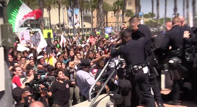 "A man in a white T-shirt and black ballcap (center) falls back after police thwart his attempt  to scale a barrier separating protestors from rally attendees at the San Diego Convention Center. A Mexican flag waves in the background. Upon hearing of the fracas, Trump quipped: ""I guess it's a good thing I'm not running for president of Mexico. And maybe if we'd had a better wall in place, the conflict could have been avoided."""