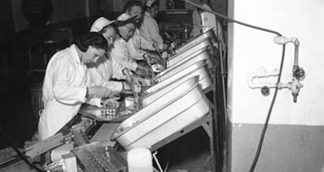 """On the Tunies production line (undated photo).  San Diego businessman C. Arnholt Smith bought some local canneries in 1948. In a 1992 interview, he told the Reader: """"One guy who worked for us got the bright idea of making hot dogs out of tuna for the Catholic trade. They were called Tunies. They tasted and looked just exactly like a hot dog. Actually tasted better than a hot dog, I think. The poor guy worked his brains out perfecting that. They were in the store, but they just didn't seem to take over.""""  You can purchase this photo at the San Diego Historical Society Research Library or online at www.sandiegohistory.org. For more information call 619-232-6203, x127."""