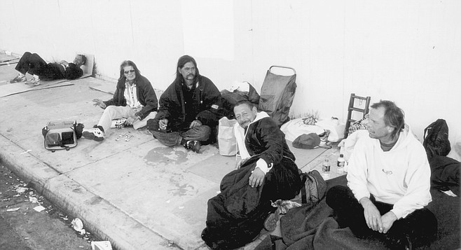 """Commercial Street homeless, from left to right: Ozzie, J. Kalei, David Clinton Reed, Matthew Castel. Reed: """"This is my family here. The homeless people are my family. That's why we're all together, and we all stick up for each other."""""""