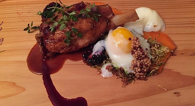 Pork shank served on a cedar board with accompaniments