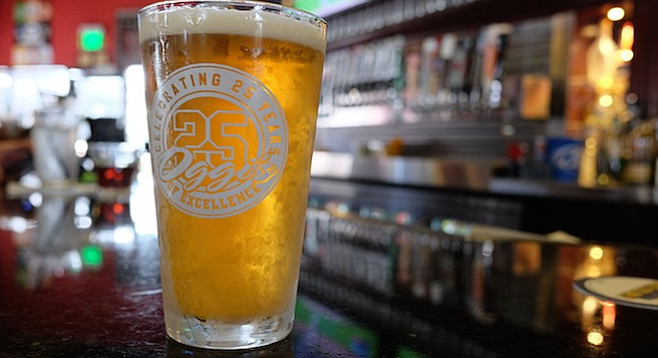 A pint of Oggi's orange wheat anniversary beer sits on a bar during a baseball game.