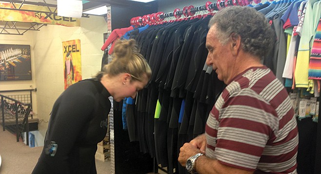 John Buono helps a customer try on a suit at South Coast