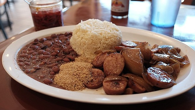 A Prato Feito calabrasa acebolado —aka the combo plate —  with beans, rice, yucca flour, sliced sausage, and onions.
