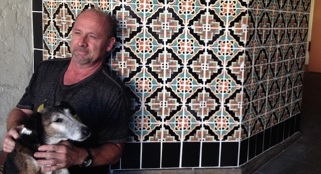 Theater owner Alan Largent and his dog Oscar leaned up against the ticket booth