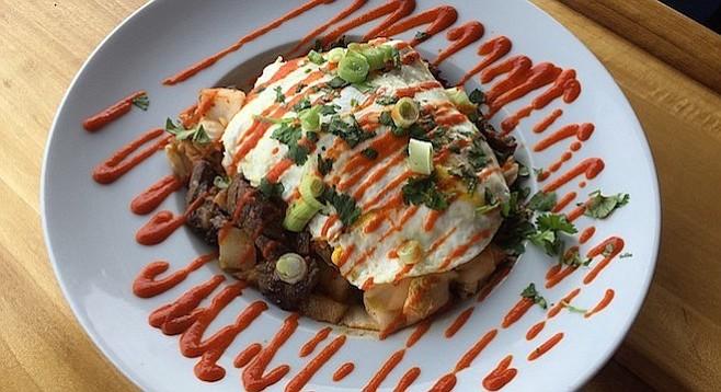 The Kim Chee Bulgogi Hash features Korean BBQ steak, kimchi, onions, potatoes, two eggs, and Sriracha. Lots of Sriracha.