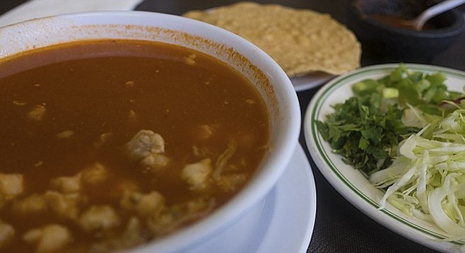 Pozole translates to hominy, derived from Aztec words describing it for what it is: a bunch of fluffy corn kernels