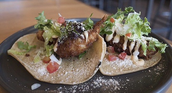 A pair of fried lobster-tail tacos topped by lettuce, tomato, onion, a dusting of cotija, and a sweet-chile aioli