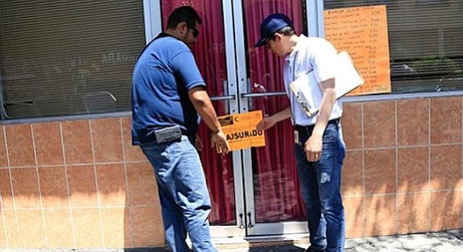 Health officials seal the door of a closed restaurant