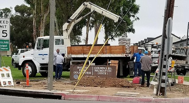 Crew installing new sign at 26th Street and Golf Course Drive