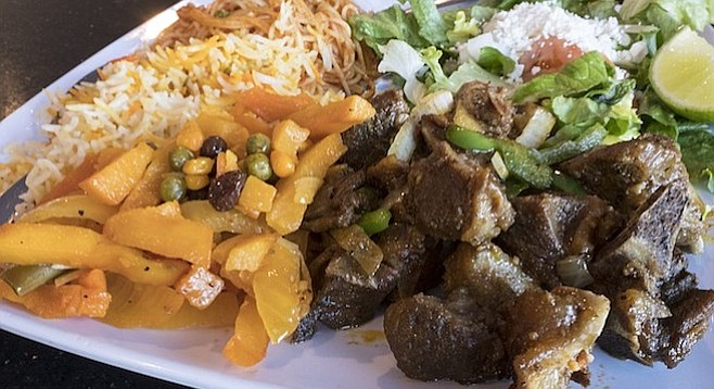 Somali dishes including goat and potatoes plus salad, rice, and pasta