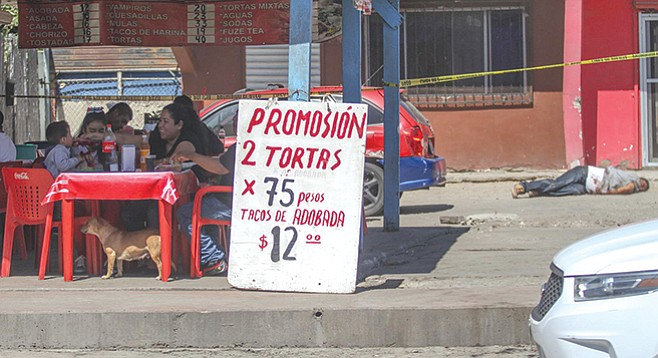 A picture posted by Frontera News went viral. It depicted a family eating happily at a dusty street taco stand, while a bloodied corpse of a man lies only a few feet away.