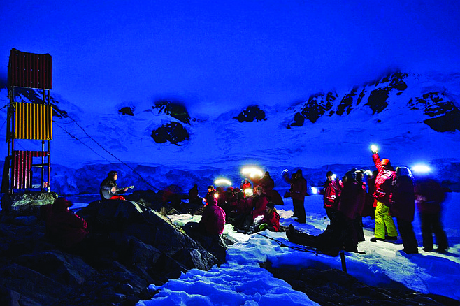 Pablo (left) gives a concert at camp in Antarctic night. Audience lights night with cell phones.